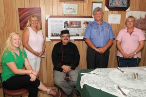 Renner Springs Roadhouse owners Alan and Christine Rendell on either side of the Borella VC memorial board, with staff members (from left); Alix Robinson, Arthur Young and Yvette Dayes,